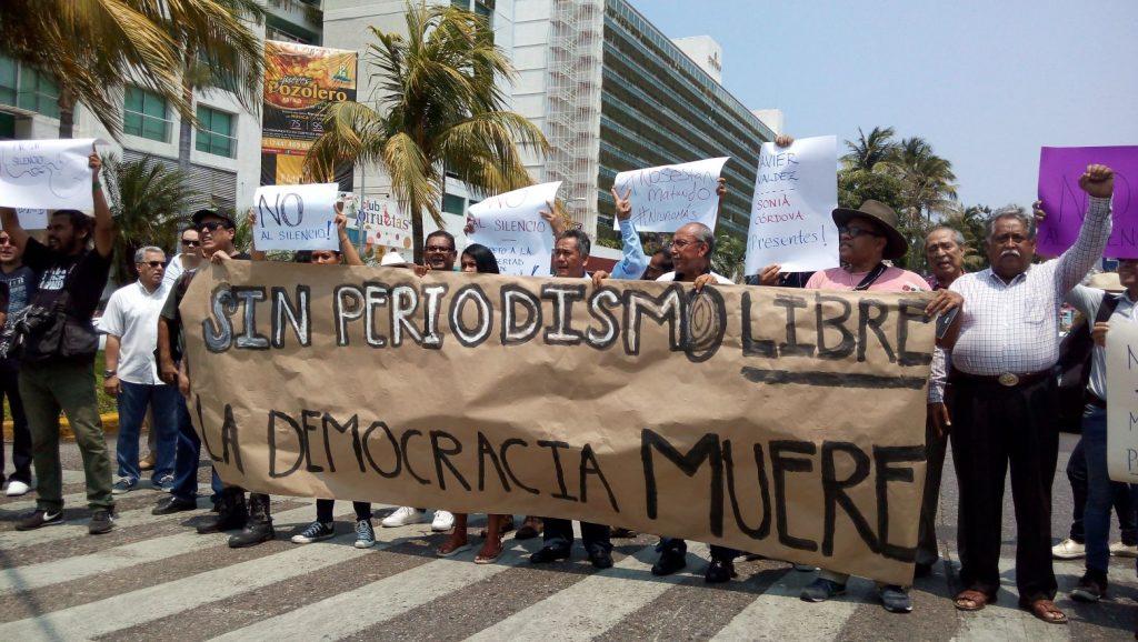 Photo de manifestation avec une banderole de soutien aux journalistes tués.