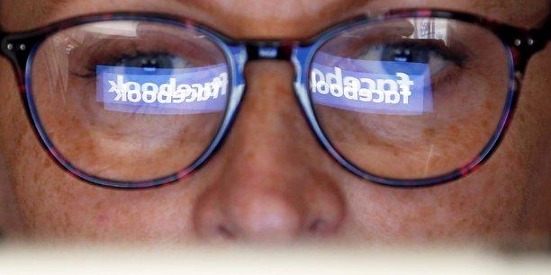 Reflets de logos Facebook dans les lunettes d'une personne agée - Crédit photo : Régis Duvignau - REUTERS