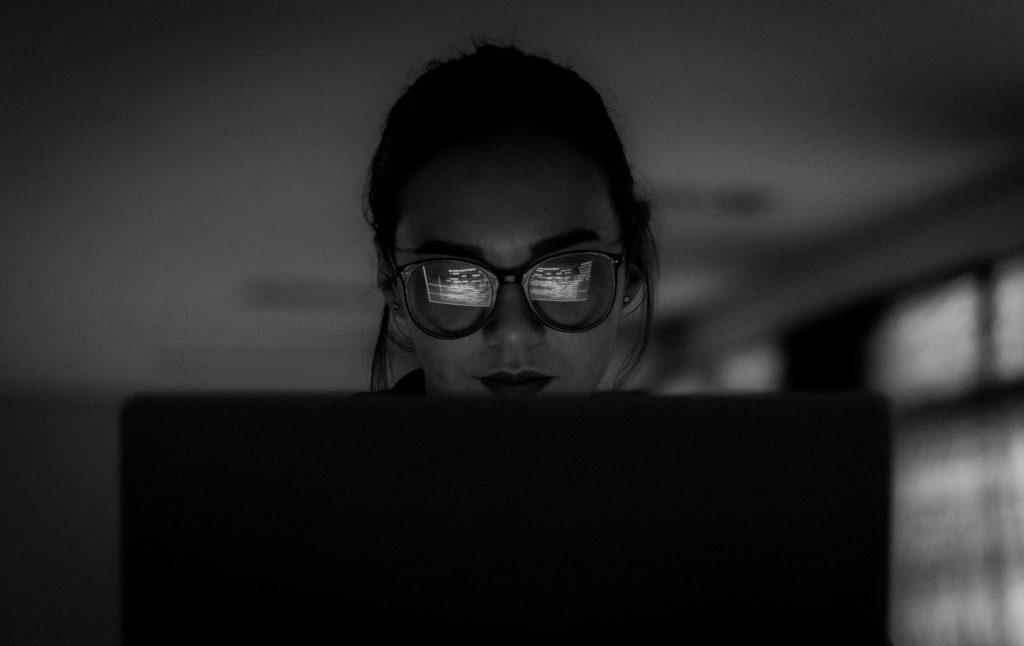 Une femme devant un ordinateur, elle porte des lumière et la photo est en noir et blanc