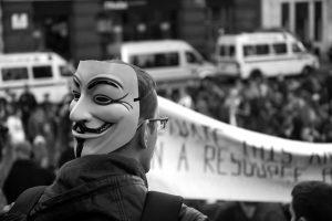 Photo du masque Anonymous dans une manifestation, elle est en noir et blanc